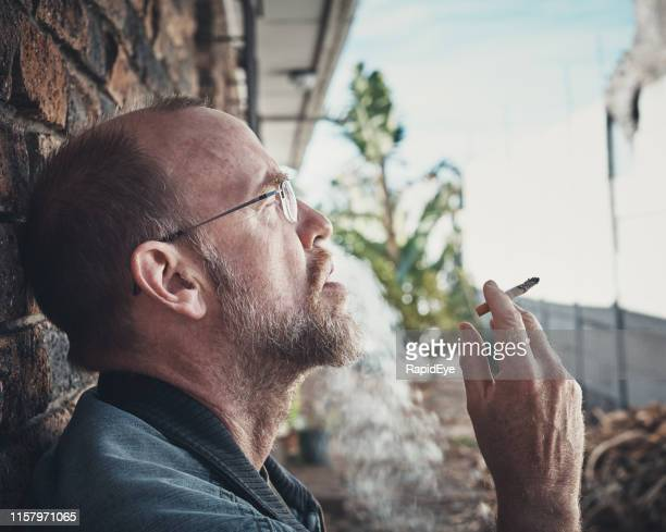 stressed mature man smoking cigarette outdoors - one mature man only stock pictures, royalty-free photos & images