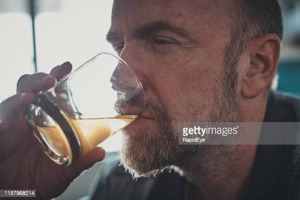 stressed middle-aged man drinks hard liquor - one mature man only stock pictures, royalty-free photos & images