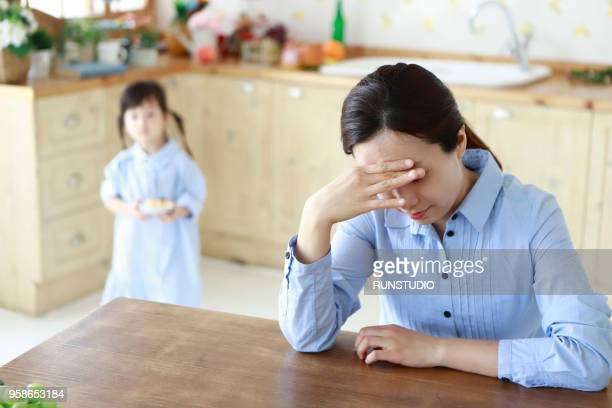 Stressed mother with little girl in kitchen