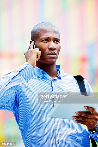 Stressé Employé de bureau à l'extérieur avec téléphone et tablette