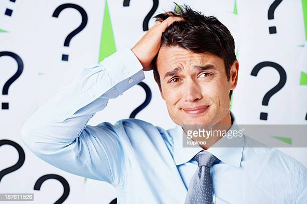 Stressed out business executive against question mark signs