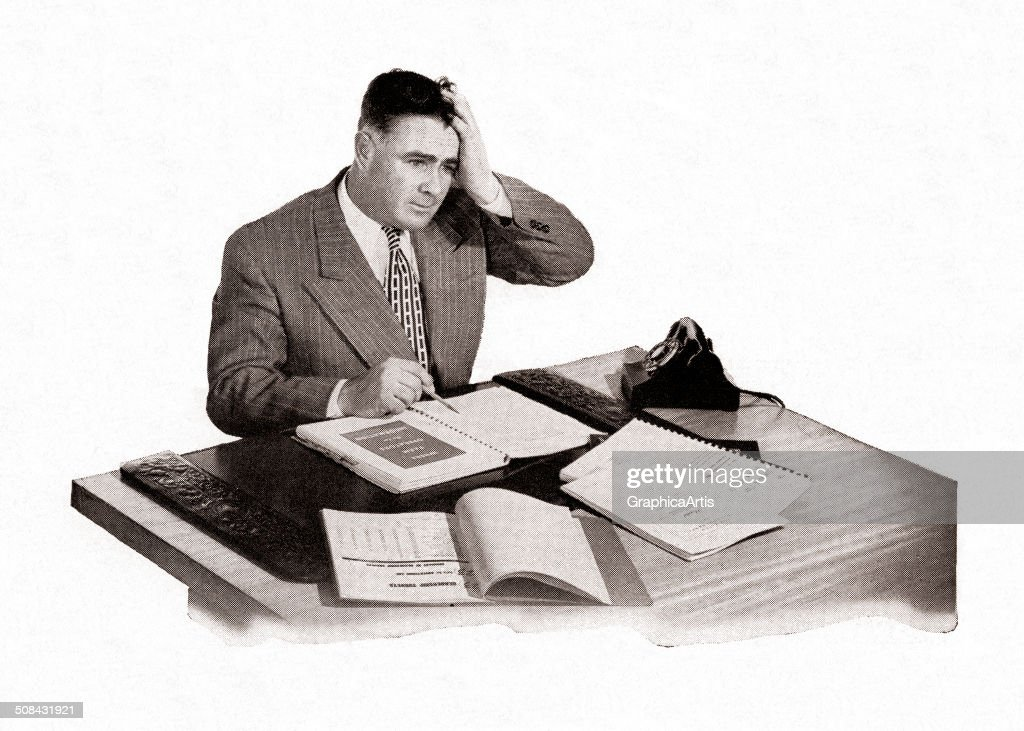 Stressed out white collar office worker with his hand to his head, sitting at his desk, 1951. Screen print.
