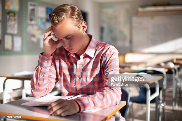 stressed student learning at desk in classroom - school detention stock pictures, royalty-free photos & images