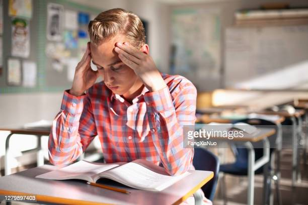 stressed teenage student sitting with book at desk - school detention stock pictures, royalty-free photos & images