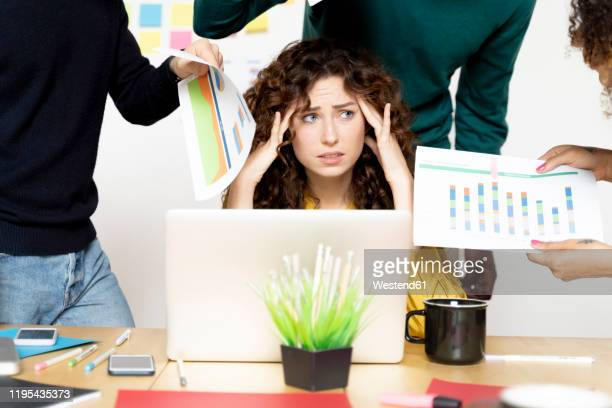 stressed woman siting at desk in office surrounded by colleagues - information overload stock pictures, royalty-free photos & images