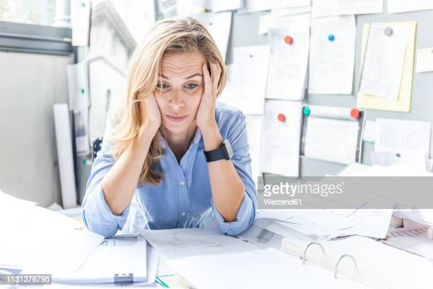 stressed woman sitting at desk in office surrounded by paperwork - stress stock-fotos und bilder