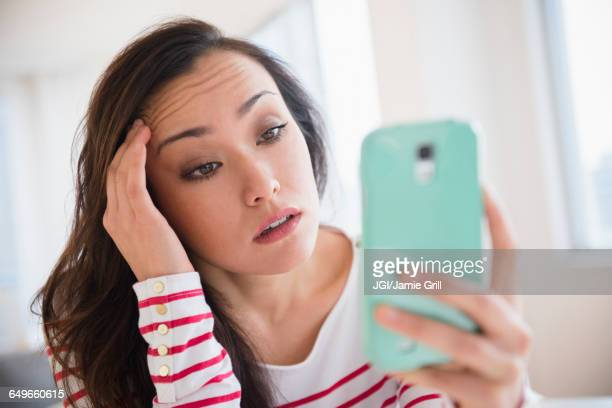 stressed woman using cell phone - misnoegd stockfoto's en -beelden
