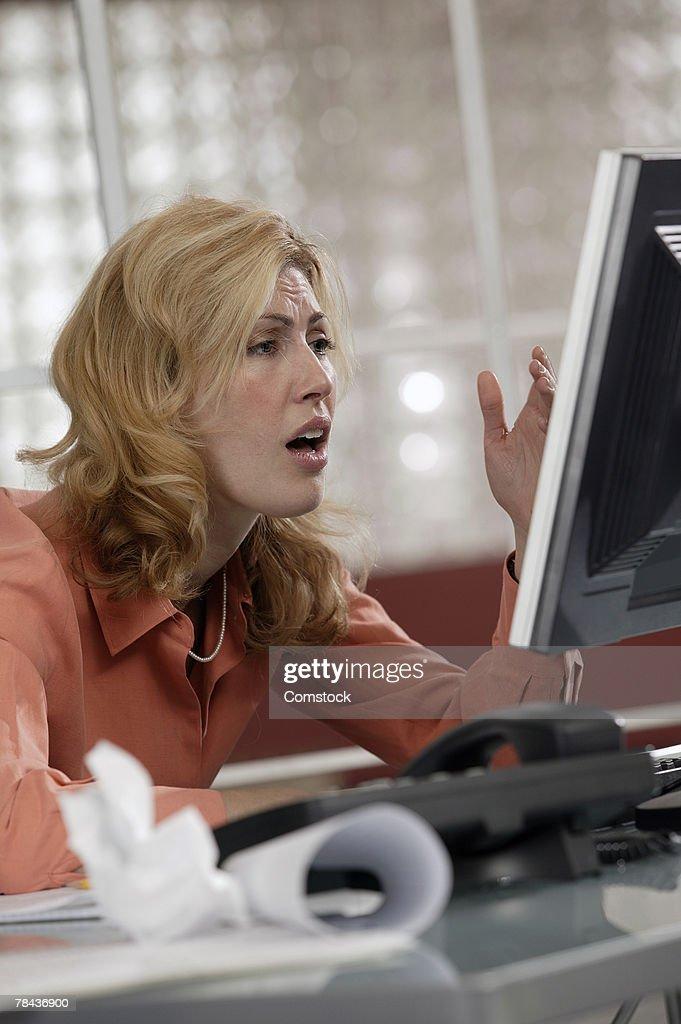 Stressed woman using desktop computer : Stockfoto