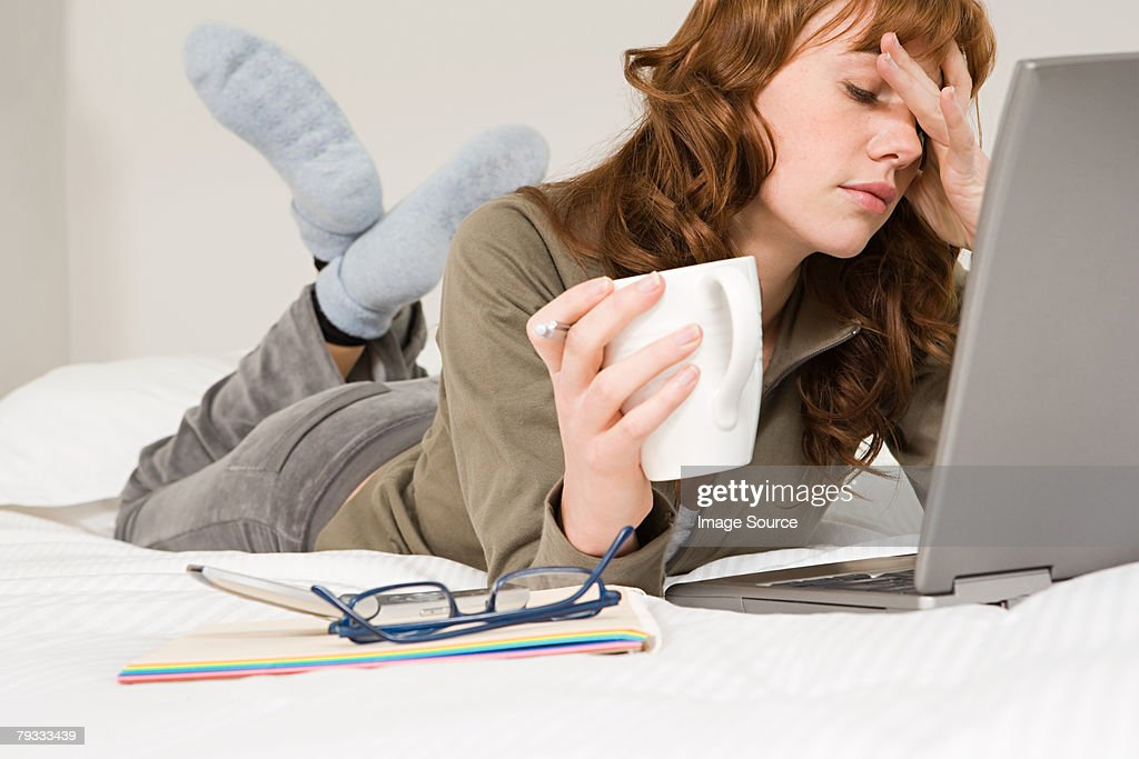 A stressed woman working on a laptop : Stock Photo