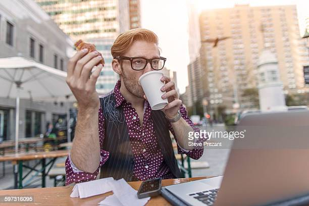 Stressed young businessman hurrying working lunch at sidewalk cafe, New York, USA