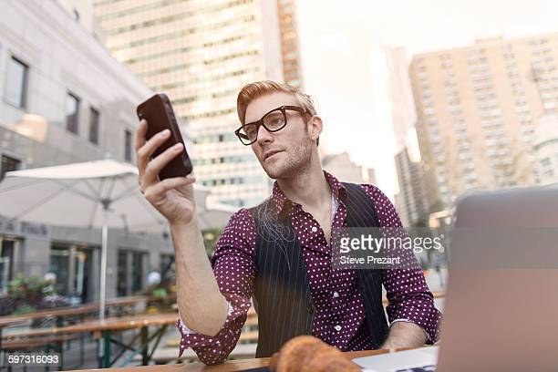 Stressed young businessman reading smartphone at sidewalk cafe, New York, USA