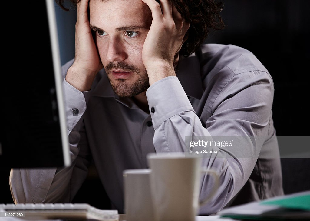 Stressed young man, working late : Stock Photo