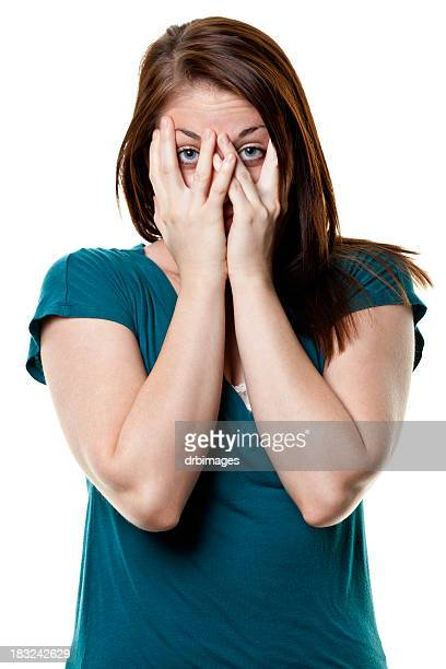 A stressed young woman covering her face with her hands