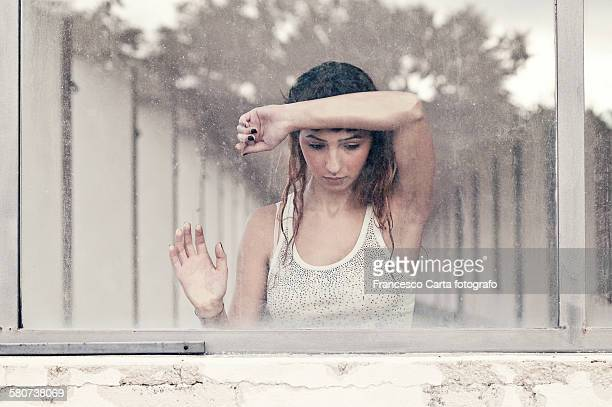 Stressed young woman looking sadly through window