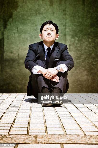 Stressed-out Japanese buisinessman sits and prays eyes closed