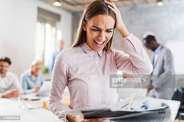 Stressigen Geschäftsfrau Probleme mit Papierkram im Büro.