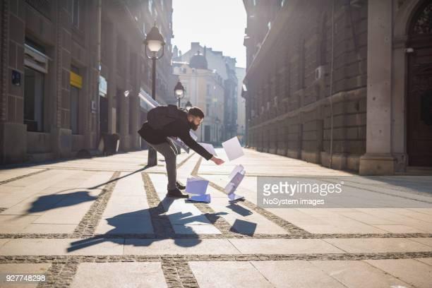 Stressigen Momente. Geschäftsmann im Freien, verschüttete Abholung Papiere auf der Straße
