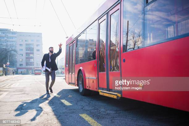 stressful moments. businessmen trying to catch the bus - bus stock photos and pictures