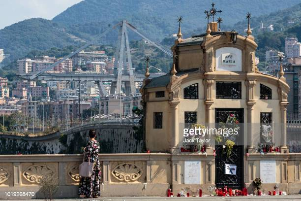 A stretch of the Morandi Bridge stands as a woman pauses beside tributes left for the victims of those killed when a section of the bridge collapsed...