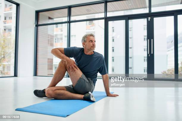 stretch those muscles - one mature man only stock pictures, royalty-free photos & images