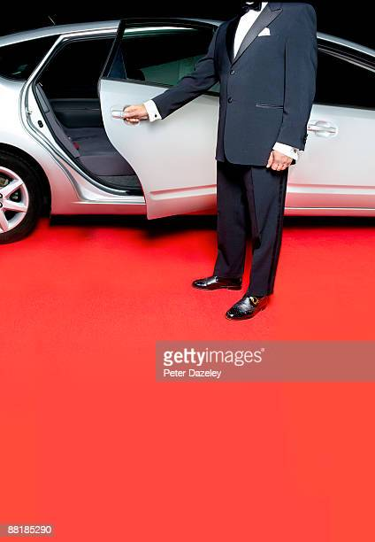 Stretched limo on red carpet with security.