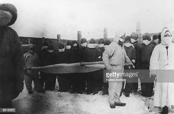 Stretcher bearers prepare to move the dead during a plague in Manchuria