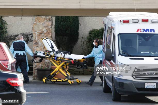 A stretcher is moved from an AMR ambulance to the Life Care Center of Kirkland where one associate and one resident were diagnosed with the novel...