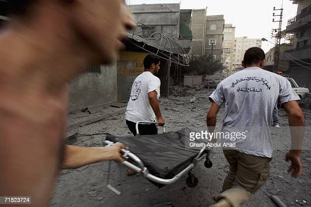 Stretcher is rushed to the scene of a fire after an Israeli air strike hit a cultural centre affiliated with Hezbollah July 26, 2006 in the southern...