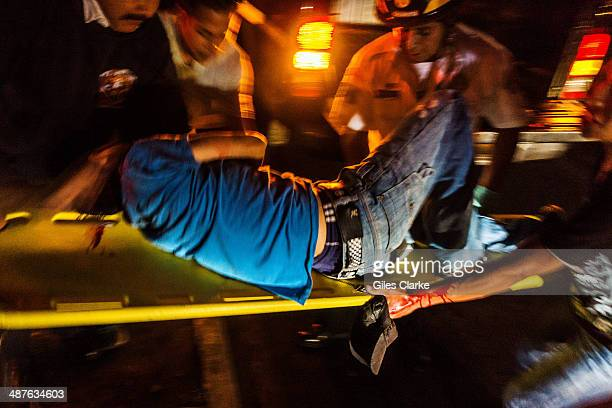 A stretcher rushes to the ambulance after a man was shot in Zone 18 June 8 2013 in Guatemala City Guatemala The bomberos voluntarios are a volunteer...