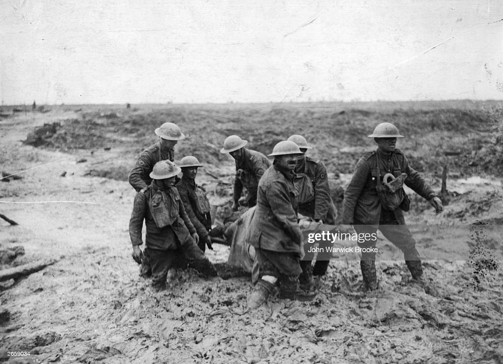 A stretcher-bearing party carrying a wounded soldier through the mud near Boesinghe during the battle of Passchendaele in Flanders.
