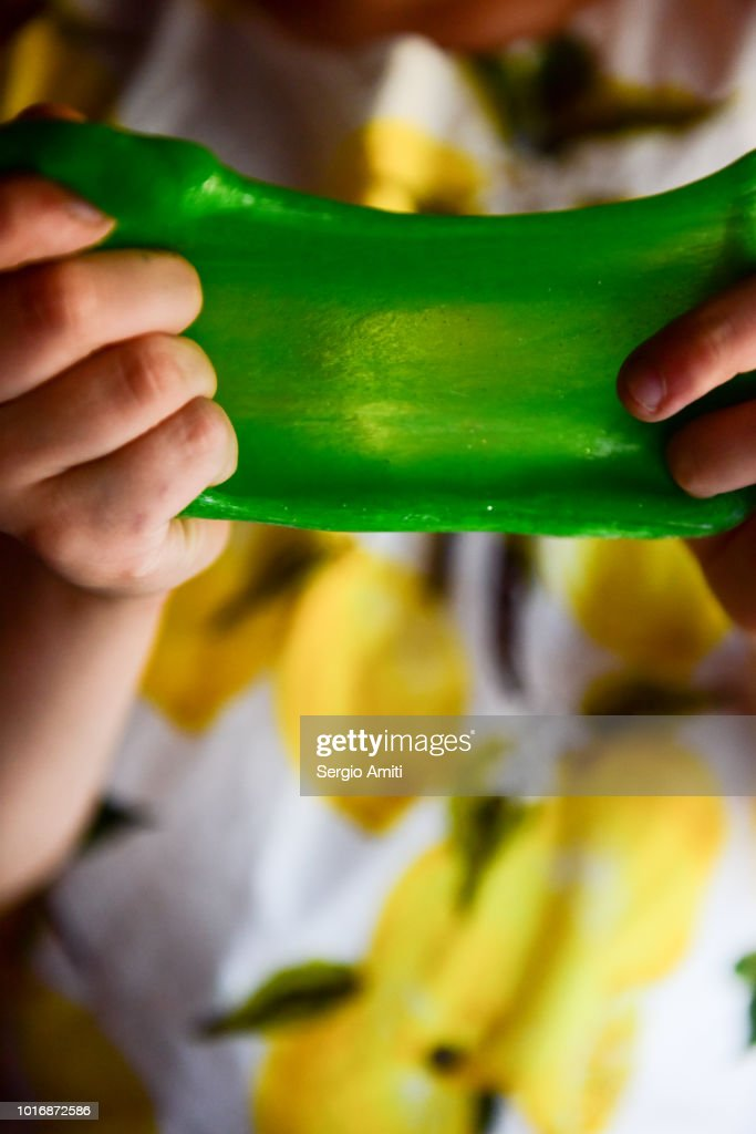Stretching a piece of green slime : Stock Photo
