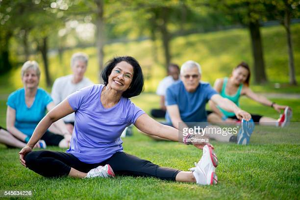 stretching after a long walk - active senior woman stock photos and pictures