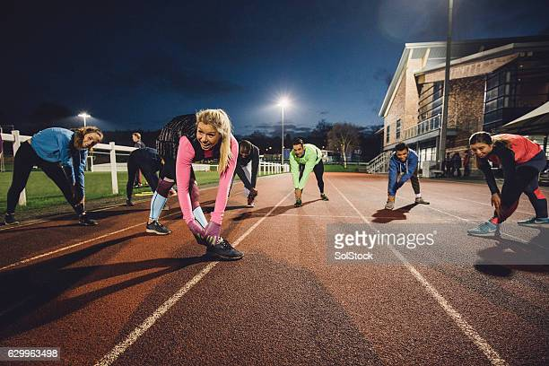 stretching before a training session at the track - athletics stock photos and pictures