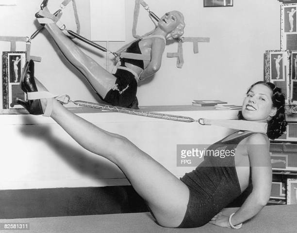 Woman uses a piece of exercise equipment made from a spring, 1935.
