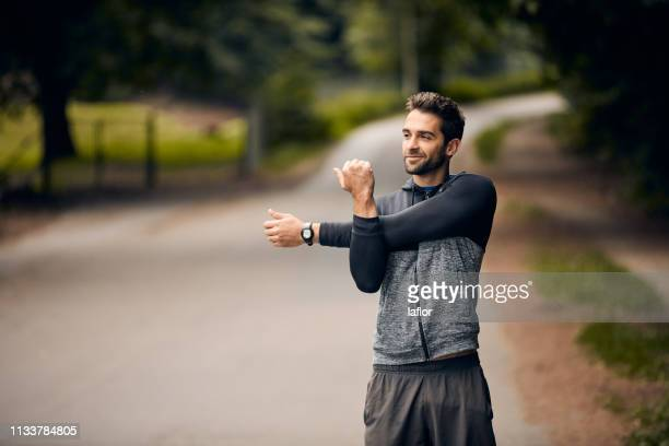 stretching for a better run - warming up stock pictures, royalty-free photos & images