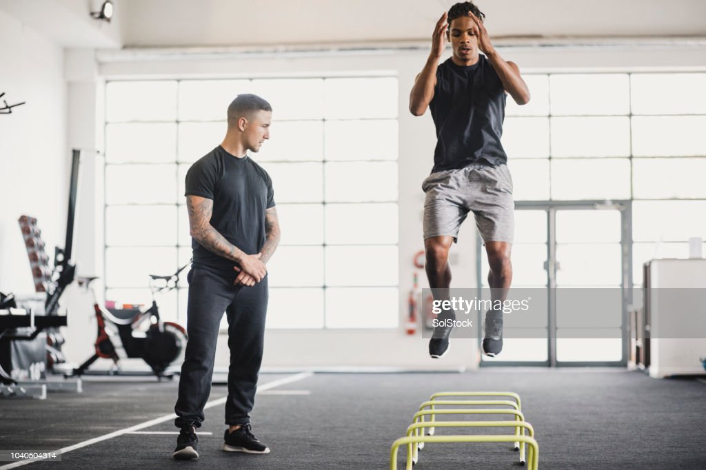 Stretching in the Gym with a Personal Trainer : Stock Photo