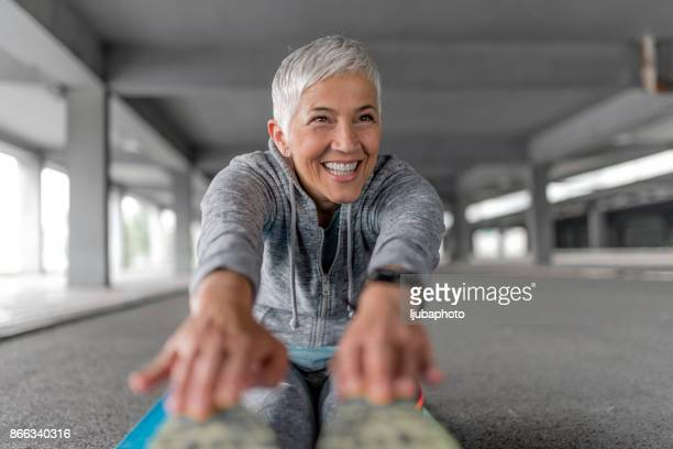 stretching is always important - older woman legs stock photos and pictures