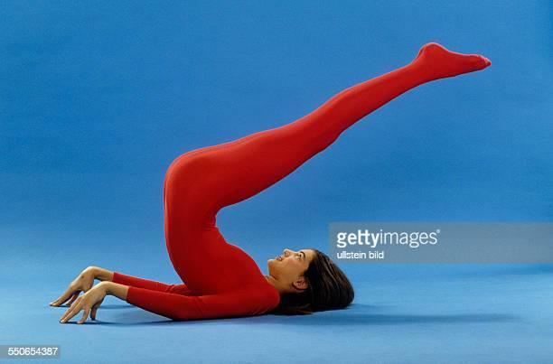 Stretching leichte Uebung Beine strecken und leicht wippen junges Mädchen roter Gymnastikanzug dunkelblonde Haare undatiert