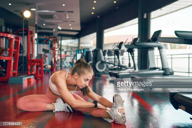stretching motivates her fitness - warming up stock pictures, royalty-free photos & images