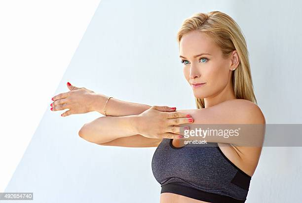 Stretching out her arms after an intense workout