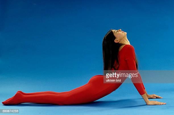 Stretching Ruecken durchbiegen mit gestreckten Armen junges Mädchen roter Gymnastikanzug dunkelblonde Haare undatiert