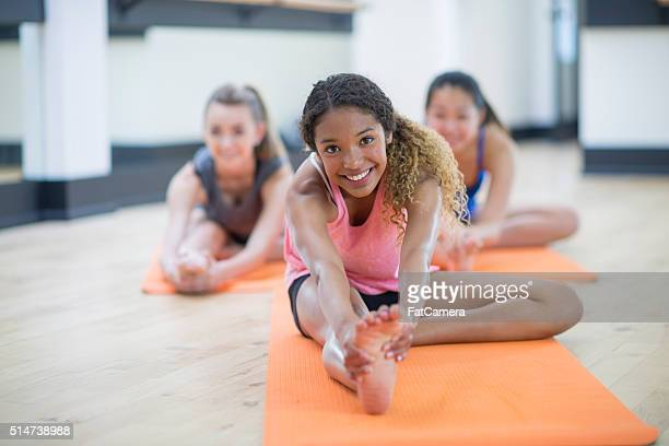 stretching to touch their toes - adolescence stock pictures, royalty-free photos & images