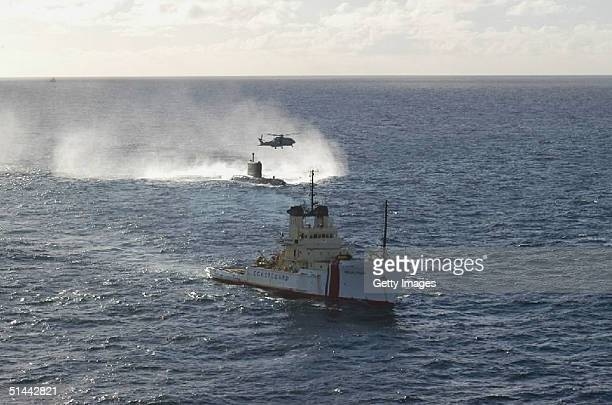 Stricken Canadian submarine HMCS Chicoutimi wallows in heavy seas October 7 2004 as the salvage vessel Anglian Prince moves into position to take the...