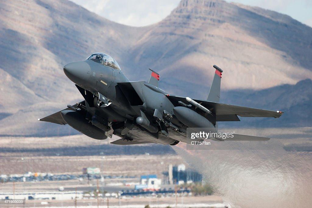 F-15E Strike Eagle flying past mountains : Stock Photo