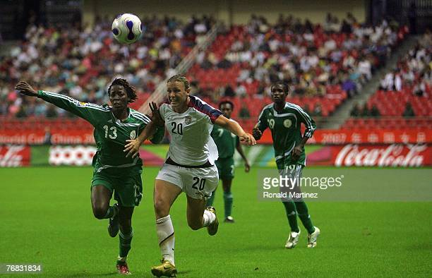 Striker Abby Wambach of USA battles for the ball with Christie George of Nigeria during the FIFA Women's World Cup 2007 Group B match at Shanghai...