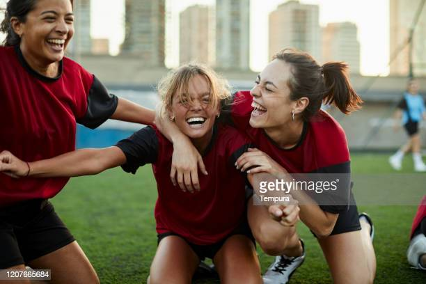 striker celebrates a goal with her team mates. - sports league stock pictures, royalty-free photos & images