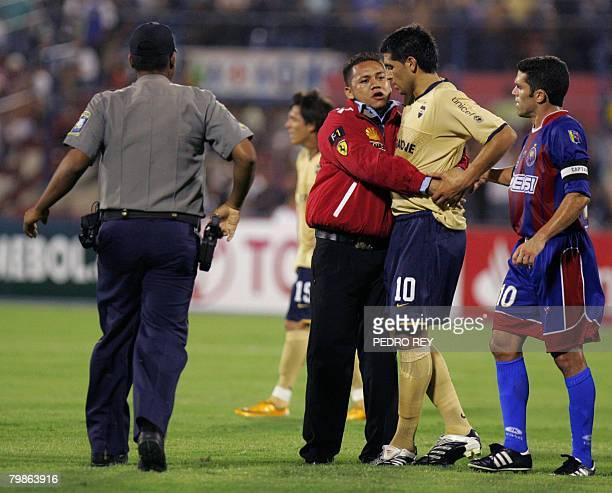 A striker embraces Argentine footballer Juan Roman Riquelme during a Libertadores Cup match between Argentina's Boca Juniors and Venezuela's Union...