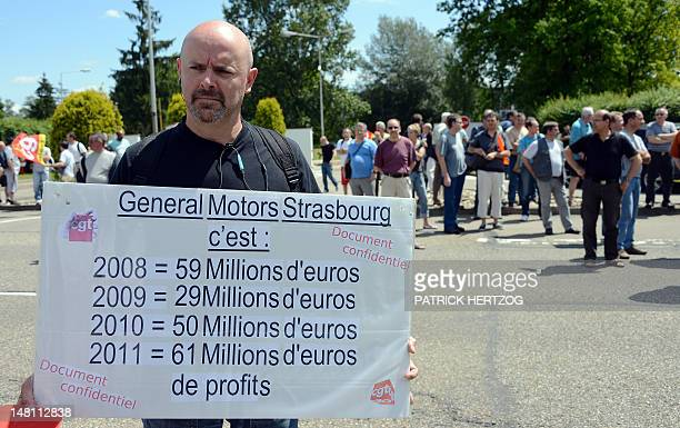 A striker holds a placard as employees of US auto giant General Motors plant of Strasbourg demonstrate on July 10 2012 in front of the company...