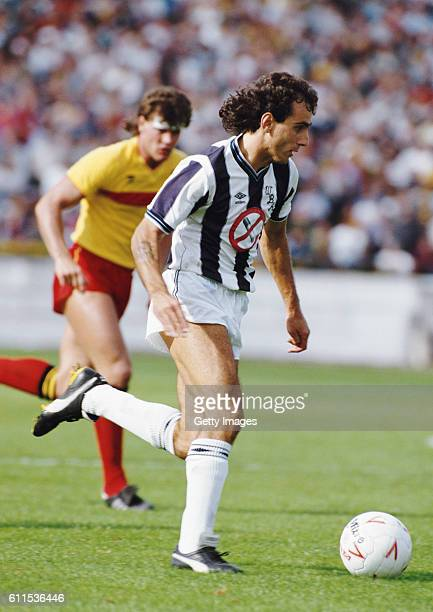 WBA striker Imre Varadi wearing the Umbro shirt with the 'No Smoking' logo advert races away from Watford defender Steve Terry during a First...