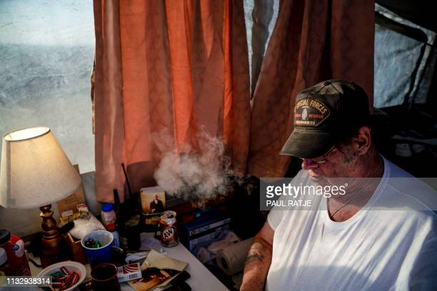 Striker the leader of Constitutional Patriots New Mexico Border Ops Team militia smokes a cigarrette inside the team's camper while discussing...